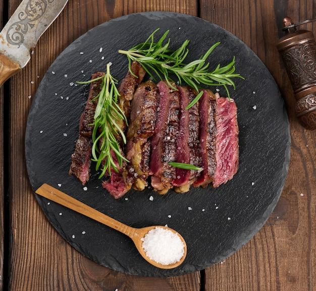 Smażony kawałek ribeye wołowego pokrojony na kawałki na czarnej desce, rzadki stopień wysmażenia. pyszny stek, widok z góry