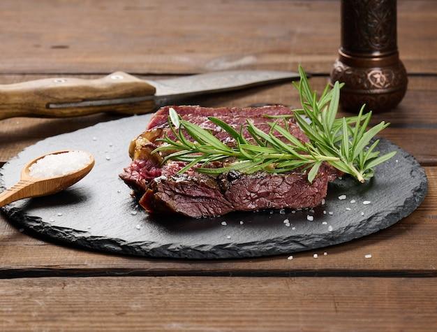 Smażony kawałek ribeye wołowego pokrojony na kawałki na czarnej desce, rzadki stopień wysmażenia. pyszny stek