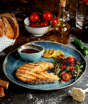Smażony kawałek ryby z ziołami i warzywami oraz sosem