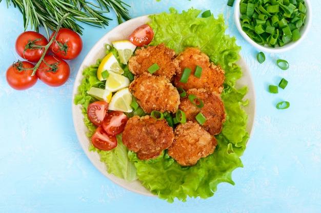 Smażony kawior z ryb rzecznych z liśćmi sałaty, pomidory czereśniowe na jasnym tle. danie dietetyczne. zdrowe odżywianie. widok z góry