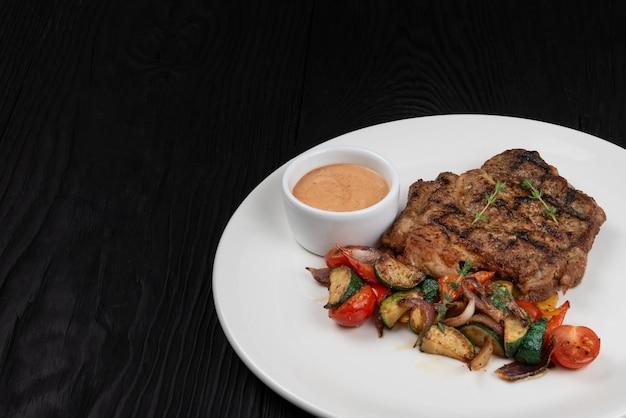 Smażony kotlet schabowy z grillowanymi warzywami i sosem na białym talerzu na czarnym drewnianym tle