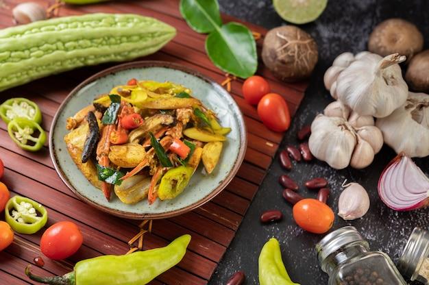Smażony krab z curry na talerzu z papryką i pomidorami.