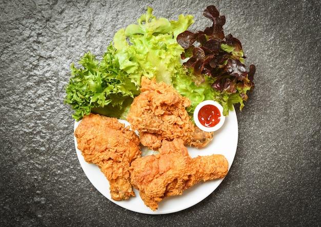 Smażony kurczak chrupiący kentucky na białym talerzu z ketchupem i sałatą sałatkową warzyw
