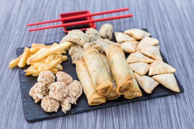 Smażony kurczak, gyozas, frytki, mięso i grzyby kulki na drewnianym stole