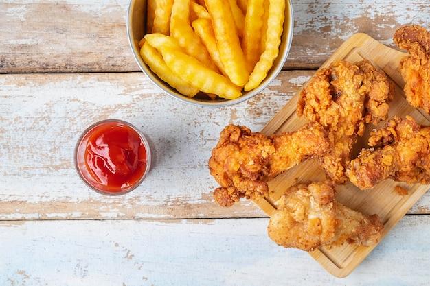 Smażony kurczak i frytki na drewnianym stole