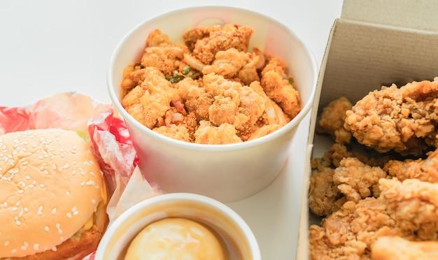 Smażony kurczak i hamburgery z ryżem, puree ziemniaczane na stole. fast foody, gotowe do spożycia z łatwością.
