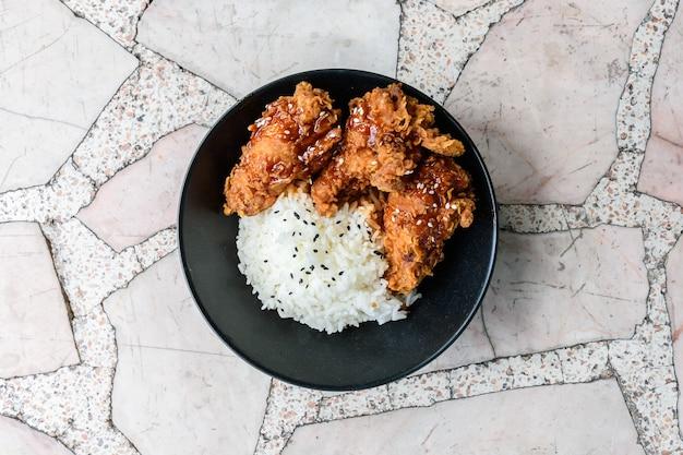 Smażony kurczak na ryżu z czerwonym sosem na marmurowym stole, widok z góry z bliska.