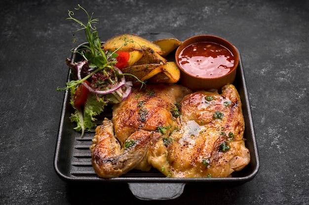 Smażony kurczak z chrupiącymi ziemniakami i sosem na patelni