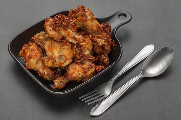 Smażony kurczak z czarną patelnią, łyżką i widelcem