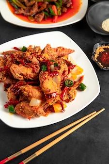 Smażony kurczak z czerwoną i zieloną papryką chili i cebulą na talerzu