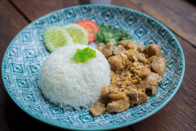 Smażony kurczak z czosnkiem i pieprzem na ryżu jest na niebieskim talerzu i brązowym drewnie jako tło.