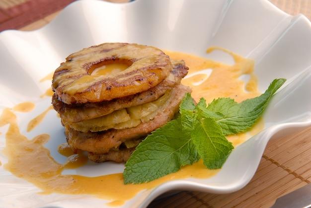 Smażony kurczak z sosem ananasowym na talerzu