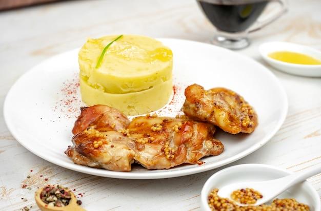 Smażony kurczak z sosem musztardowo-miodowym z puree ziemniaczanym na białym talerzu