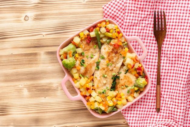 Smażony kurczak z warzywami kukurydzianymi i brokułami na drewnianym tle. widok z góry.