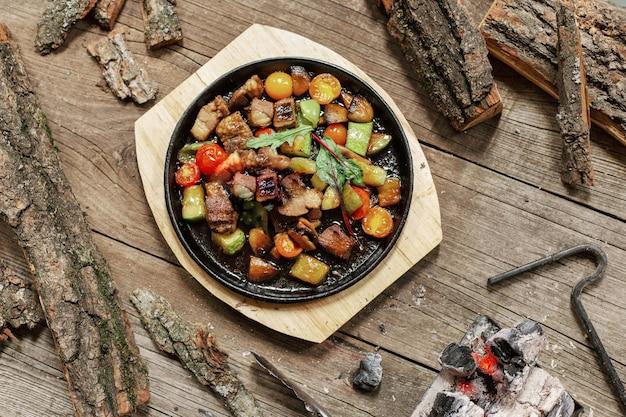 Smażony kurczak z warzywami na patelni na drewnianym tle.