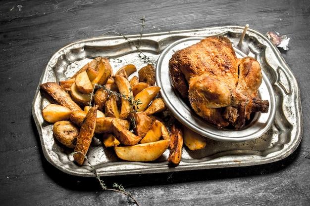 Smażony kurczak z ziemniakami na tacy na czarnej tablicy.