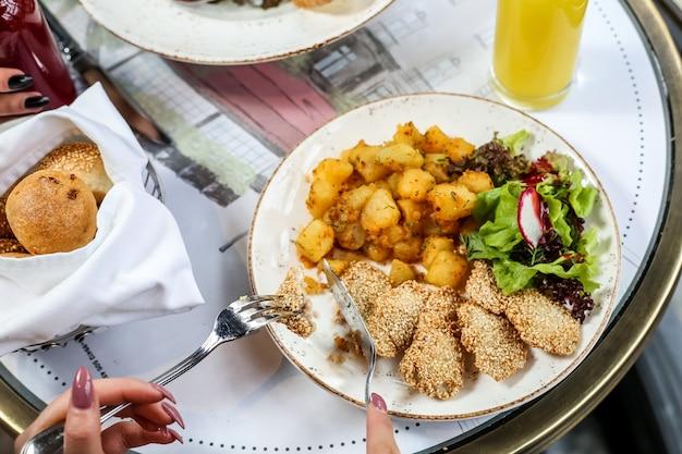 Smażony kurczak z ziemniakami, rzodkiewką, sałatą i bułeczkami