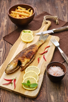 Smażony labraks ze smażonym ziemniakiem na drewnianej desce do krojenia.
