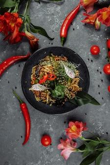 Smażony makaron i warzywa w czarnej misce. pyszne, pożywne dania kuchni azjatyckiej.