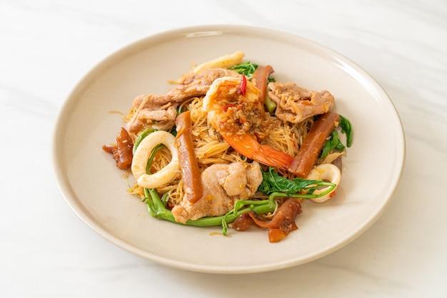 Smażony makaron ryżowy i mimoza wodna z mieszanką mięs - azjatyckie jedzenie