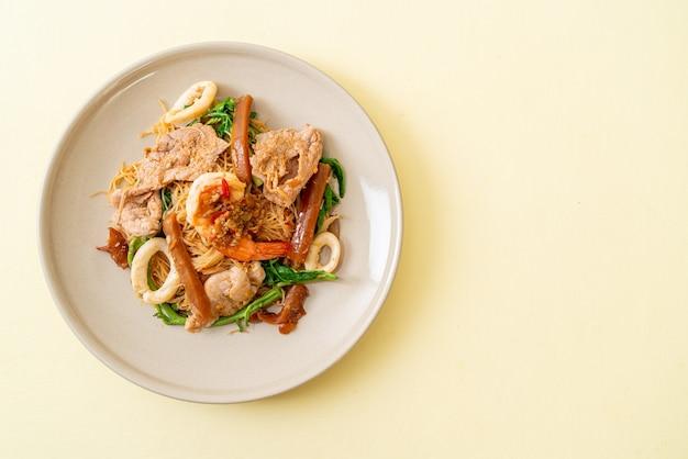 Smażony makaron ryżowy i mimoza wodna z mieszanym mięsem. azjatycki styl żywności