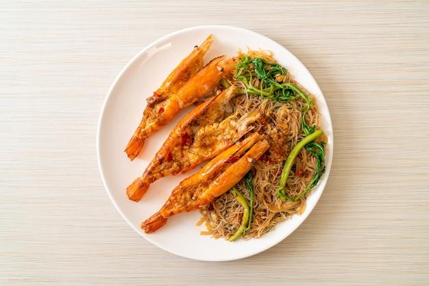 Smażony makaron ryżowy i mimozy wodne z krewetkami rzecznymi na talerzu