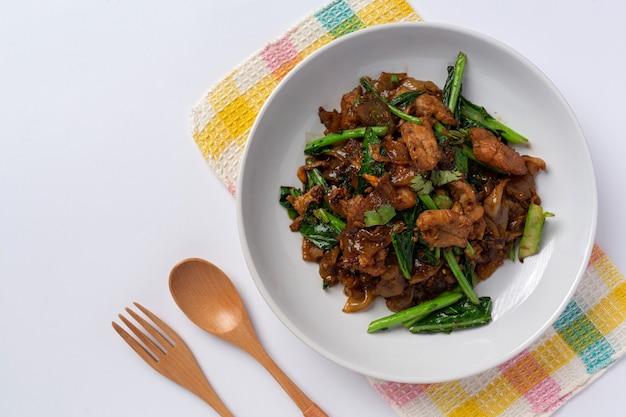 Smażony makaron ryżowy wymieszać z sosem sojowym i wieprzowiną na białym tle