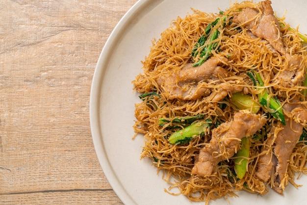 Smażony makaron ryżowy z makaronem wermiszelowym z czarnym sosem sojowym i wieprzowiną - azjatyckie jedzenie