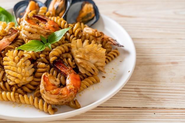 Smażony makaron spiralny z owocami morza i sosem bazyliowym - fusion food style