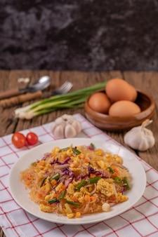 Smażony makaron szklany wymieszaj z jajkami i połóż na talerzu na białej czerwonej szmatce.