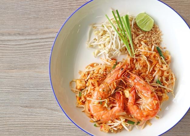 Smażony makaron w stylu tajskim zwany pad thai z krewetkami rzecznymi podawanymi na drewnianym stole