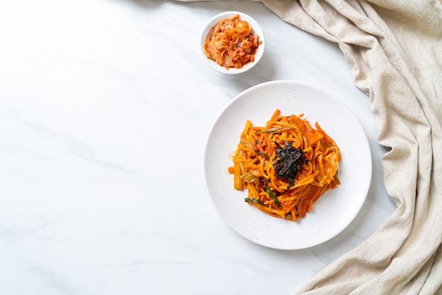 Smażony makaron wymieszaj z koreańskim pikantnym sosem i warzywami