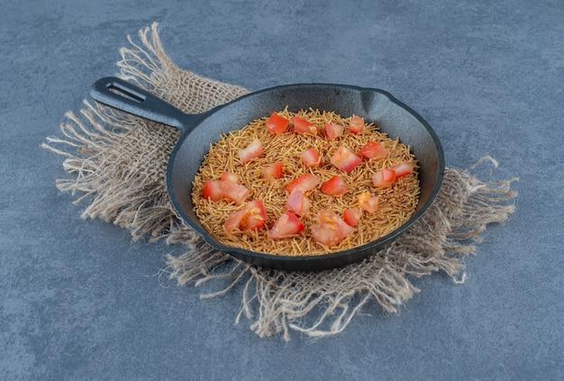 Smażony makaron z plastrami pomidora na czarnej patelni.