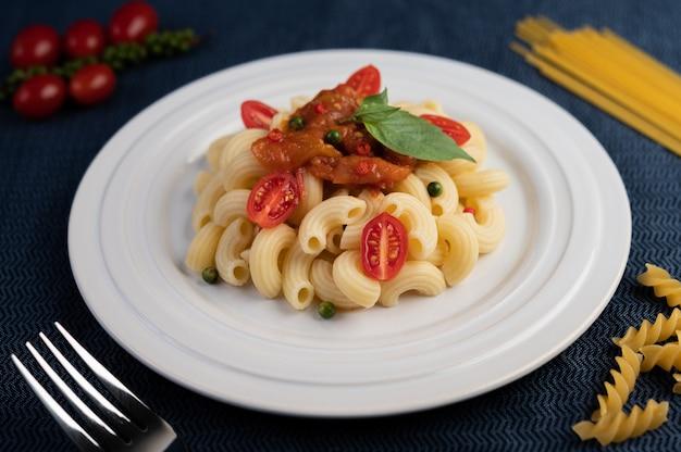 Smażony makaron z pomidorami, chili, ziarnami pieprzu i bazylią w białym naczyniu.