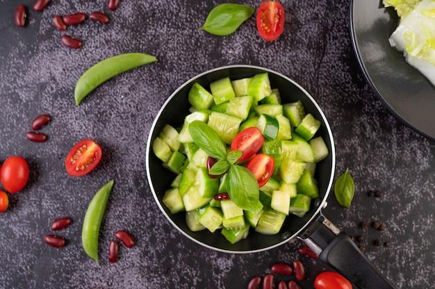 Smażony ogórek z pomidorami i czerwoną fasolą na patelni.
