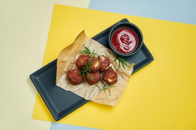 Smażony panierowany ser mozzarella na papierze rzemieślniczym ze słodkim sosem na s. przekąska do piwa