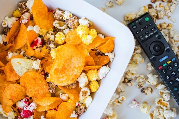 Smażony popcorn i frytki w misce na białym tle i kontrolerze telewizora, niski kąt widzenia