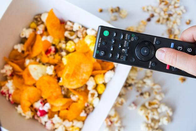 Smażony popcorn i frytki w misce na białym tle, ręka trzymająca kontroler tv, niski kąt widzenia