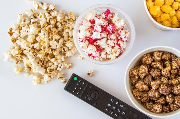 Smażony popcorn na białym tle i kontroler tv