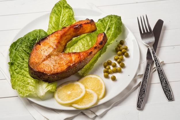 Smażony pstrąg z kawałkiem sałaty cytrynowej i zielonym groszkiem