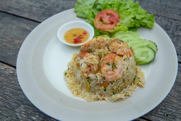Smażony ryż po tajsku z krewetkami lub khao pad goong na białym talerzu.