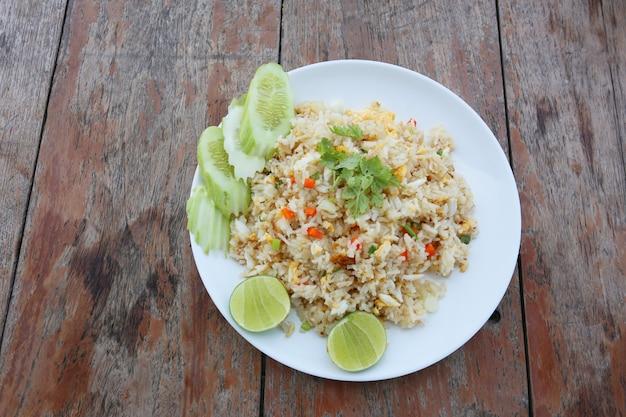 Smażony ryż w białym talerzu na starym brązowym drewnianym stole.