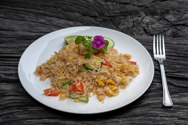 Smażony ryż z krewetkami i warzywami w białym naczyniu na starym drewnianym stole, z bliska. kuchnia tajska, kuchnia tajska. smażony ryż z owocami morza w restauracji