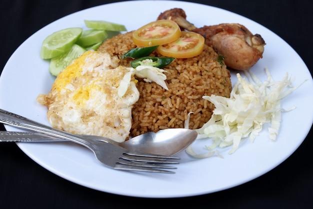 Smażony ryż z kurczakiem, jajkami, warzywami na białym tle na czarnym tle