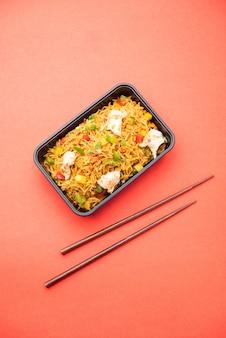 Smażony ryż z kurczakiem zapakowany w czarny plastikowy pojemnik do zamówienia dostawy żywności online. popularny chiński przepis indyjsko-chiński!