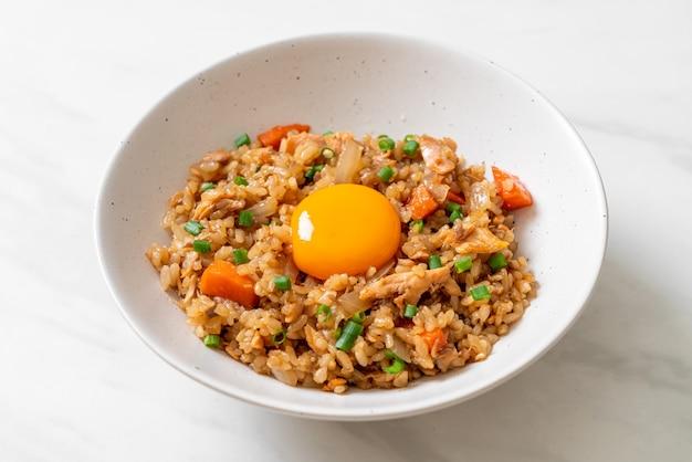 Smażony ryż z łososiem z marynowanym jajkiem na wierzchu. azjatycki styl żywności