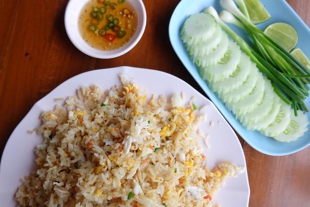 Smażony ryż z warzywami, domowym krabem i smażonymi jajkami serwowany na talerzu.