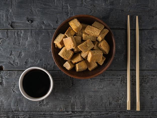 Smażony ser tofu, sos sojowy w białej misce i pałeczki na drewnianym stole. przystawka z grillowanego sera. leżał na płasko.