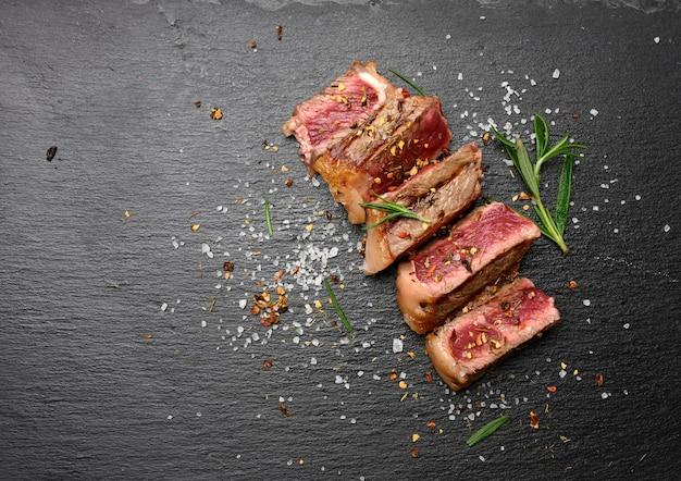 Smażony stek wołowy new york rostbef w plastrach na czarnej powierzchni z przyprawami, rzadki stopień wypieczenia, widok z góry