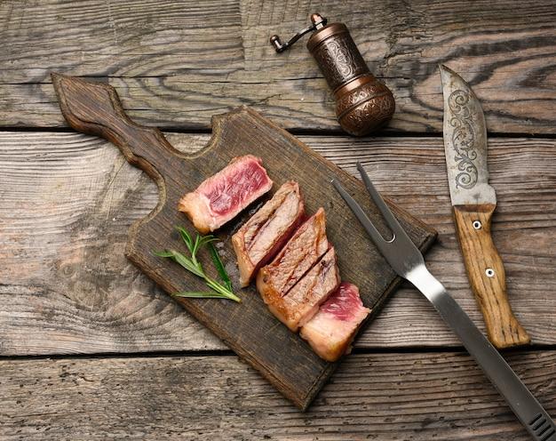 Smażony stek wołowy new york rostbef w plastrach na drewnianej desce do krojenia, rzadki stopień wypieczenia, widok z góry